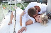 A man kissing a woman in the neck while lying on the deck.