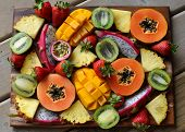 stock photo of passion fruit  - Tropical and exotic fruits sliced and arranged artistically on a wooden board - JPG