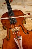 stock photo of viola  - Old viola and arch on a wooden background - JPG