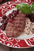 Grilled beef steak with cooked rice and cranberry sauce