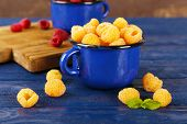 Red and yellow raspberries in dark blue metal mugs on cutting board on wooden table on brown backgro
