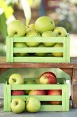 Juicy apples in wooden boxes, outdoors