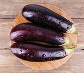 Aubergines on round cutting board on wooden background