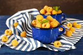 Yellow raspberries in dark blue mugs on napkin on table on dark background