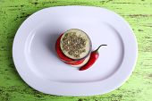 Slices of aubergines with tomatoes and chilly pepper on plate on wooden background