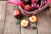 Sweet plums in wicker basket on wooden background