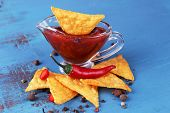 Tasty nachos and bowl with sauce on color wooden background