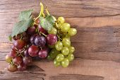 Bunches of different kinds of grapes on wooden background