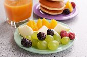 Pancake with fruits and berries on plate on table close up