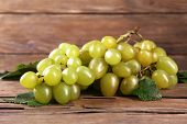 Bunch of ripe grape on wooden table on wooden wall background