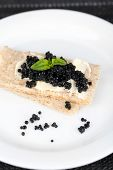 Slices of bread with butter and black caviar on plate on dark fabric background closeup