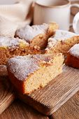 Pieces of delicious cake on cutting board with cup of coffee on wooden table