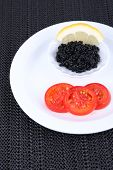 Black caviar with slices of tomato on plate on dark fabric background