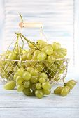 Ripe grapes in metal basket on wooden table on light background