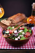 Bowl of Greek salad served with olive oil and glass of wine on napkin on wooden table on dark backgr