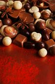 Different kinds of chocolates on red background