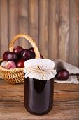 stock photo of jar jelly  - Tasty plum jam in jar and plums on wooden table close - JPG