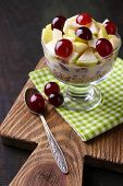 Healthy breakfast - yogurt with  fresh grape and apple slices and muesli served in glass bowl, on wo