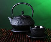Chinese traditional teapot on bamboo mat, on dark color background