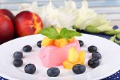 Heart shaped cake with blueberries and fruits on plate on polka dot table cloth