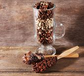 Glass and spoons with coffee beans on wooden table on wooden background