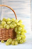 Ripe grapes in wicker basket on wooden table on light background