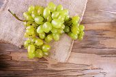 Bunch of ripe grape on napkin on wooden table on wooden wall background