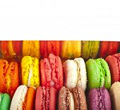 Assortment of multicolored macaroon in cardboard box . top view isolated on white