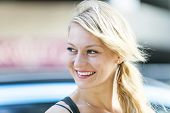 Candid portrait of young blonde woman smiling with copy space