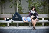 Romantic interracial young couple relaxing on park bench outside