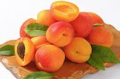 detail of ripe apricots on wooden cutting board