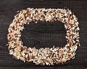 Frame made of colorful blend several varieties of whole grain rice in a rustic wooden surface backgr