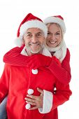 Portrait of happy mature couple wearing santa hats over white background