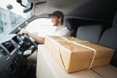 foto of foreground  - Delivery driver driving van with parcels on seat outside the warehouse - JPG