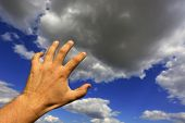man hand against sky background