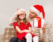 family, christmas, x-mas, happiness and people concept - smiling father surprise daughter with gift