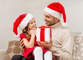 family, christmas, x-mas, happiness and people concept - smiling father giving daughter gift box