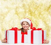 holidays, presents, christmas, childhood and people concept - smiling girl in santa helper hat with