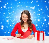 christmas, holidays, celebration, greeting and people concept - smiling woman with gift box writing