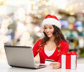 christmas, holidays, technology and shopping concept - smiling woman in santa helper hat with gift b