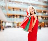 sale, gifts, christmas, holidays and people concept - smiling woman in red dress with shopping bags