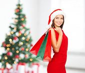 sale, gifts, holidays and people concept - smiling woman in red dress with shopping bags over living