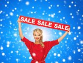 sale, shopping, christmas, holidays and people concept - smiling woman in red dress with red sale si