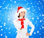 christmas, winter, happiness, holidays and people concept - smiling woman in santa helper hat with g
