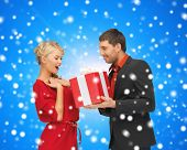 christmas, holidays, celebration and people concept - smiling man and woman with present over blue o