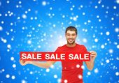 sale, shopping, christmas, holidays and people concept - smiling man in red t-shirt with sale sign o