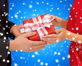 christmas, holidays, celebration and people concept - close up of man and woman with present over bl
