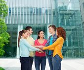 friendship, education, business, gesture and people concept - group of smiling teenagers with hands