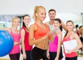 sport, fitness, technology, internet and healthcare concept - smiling sporty woman with smartphone a