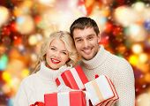christmas, holidays, happiness and people concept - smiling man and woman with presents over red lig